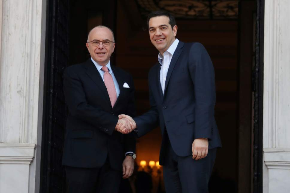 Greece's Prime Minister Alexis Tsipras, right, and his French counterpart Bernard Cazeneuve shake hands before their meeting at Maximos Mansion in Athens, Friday, March 3, 2017. Cazeneuve and Finance Minister Michel Sapin are in Athens for talks as Greek officials were expected to ask for assistance in overcoming sticking points in the bailout talks. (AP Photo/Yorgos Karahalis)