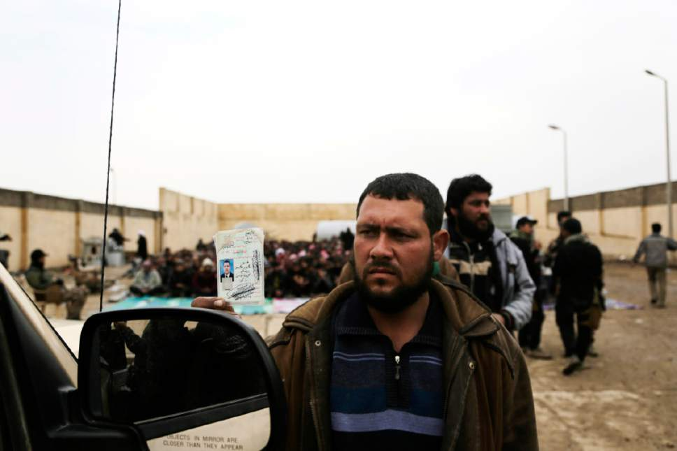 A man holds up his identification card to an Iraqi intelligence officer screening men and boys fleeing Islamic State group-held Mosul on Friday, March 3, 2017. Security forces say they worry IS fighters could be escaping the city among the thousands who are fleeing clashes and a worsening humanitarian situation. (AP Photo/Susannah George)