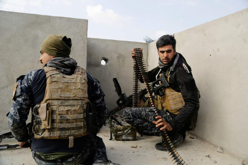Iraqi federal police forces man a position on a roof of a house in on the edge of Mosul's Mamun neighborhood on Friday, March 3, 2017. Iraqi forces are still fighting to secure a belt of districts along the city's southwestern edge after launching an operation to retake western Mosul from the Islamic State group nearly two weeks ago. (AP Photo/Susannah George)