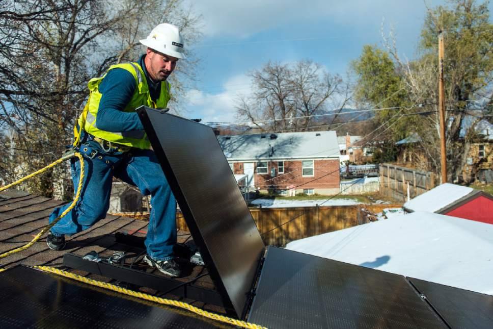 Chris Detrick  |  The Salt Lake Tribune Creative Energies lead electrician Justin Therrien installs solar panels on top of a home in Salt Lake City in December.