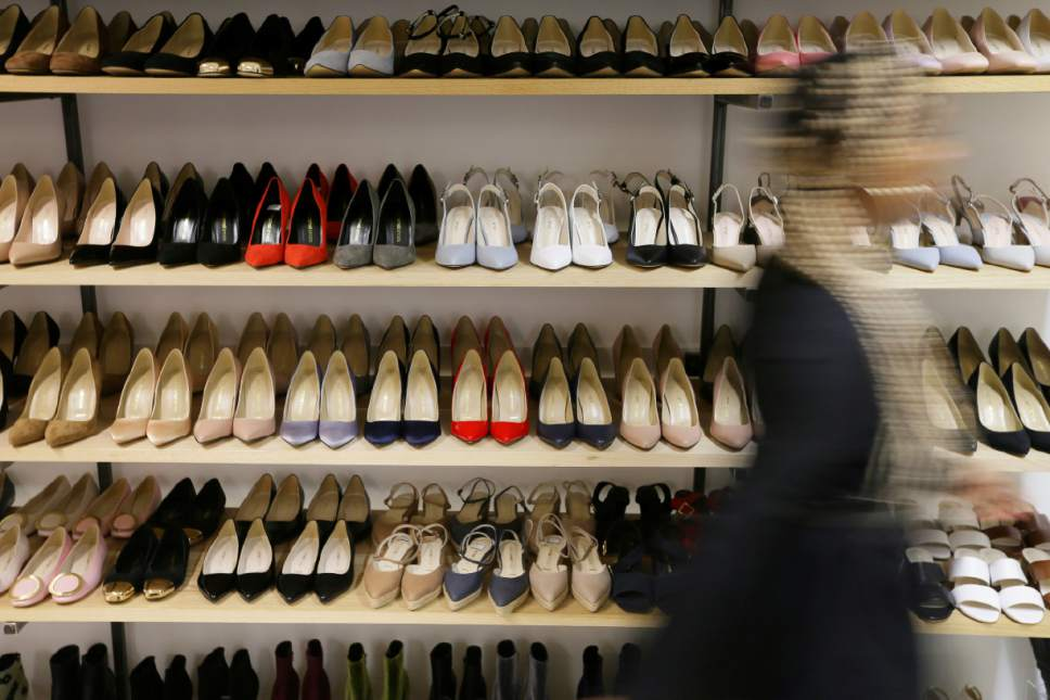 "A person poses for a picture walking past high heels on display in the Pretty Small Shoes store in Bloomsbury, London, Monday, March 6, 2017. Members of Parliament on Monday will debate banning mandatory workplace high heels, in response to a petition by a receptionist who was sent home for wearing flat shoes. The petition, which calls formal workplace dress codes ""outdated and sexist,"" gathered more than 150,000 signatures, making it eligible for a non-binding debate in Parliament. (AP Photo/Tim Ireland)"