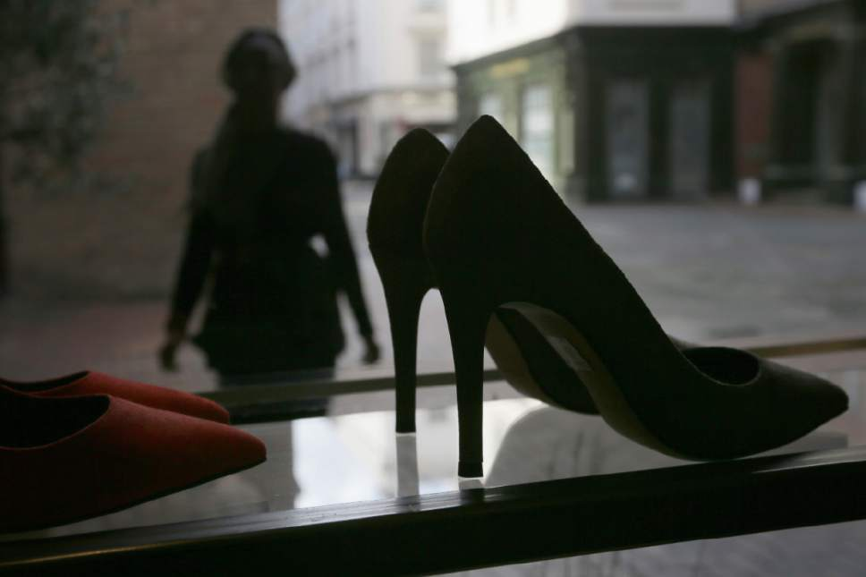 "A person looks at high heels on display at the Pretty Small Shoes store in Bloomsbury, London, Monday, March 6, 2017. Members of Parliament on Monday will debate banning mandatory workplace high heels, in response to a petition by a receptionist who was sent home for wearing flat shoes. The petition, which calls formal workplace dress codes ""outdated and sexist,"" gathered more than 150,000 signatures, making it eligible for a non-binding debate in Parliament. (AP Photo/Tim Ireland)"