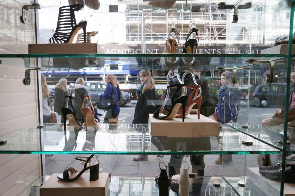 "People walk past high heels on display in a shoe store on Oxford Street, London, Monday, March 6, 2017. Members of Parliament on Monday will debate banning mandatory workplace high heels, in response to a petition by a receptionist who was sent home for wearing flat shoes. The petition, which calls formal workplace dress codes ""outdated and sexist,"" gathered more than 150,000 signatures, making it eligible for a non-binding debate in Parliament. (AP Photo/Tim Ireland)"