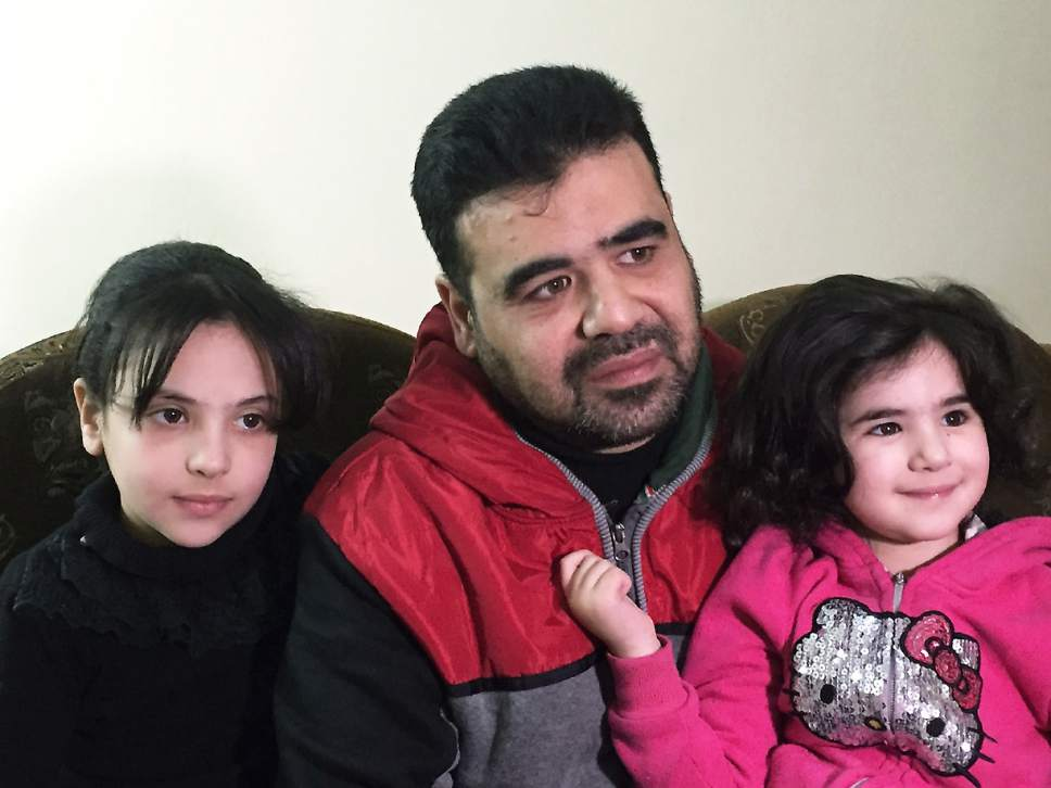 Syrian refugee Mahmoud Mansour, 43, is shown in this photo, taken Monday, March 6, 2017, in Amman, with his daughters Ruba, 9, and Sahar,  3. Mansour, who has been undergoing vetting for resettlement to the U.S. for the past year, says he was devastated by President Donald Trump's travel ban and remains confused about how the revised version could affect his hopes for future in the U.S. (AP Photo/Karin Laub)