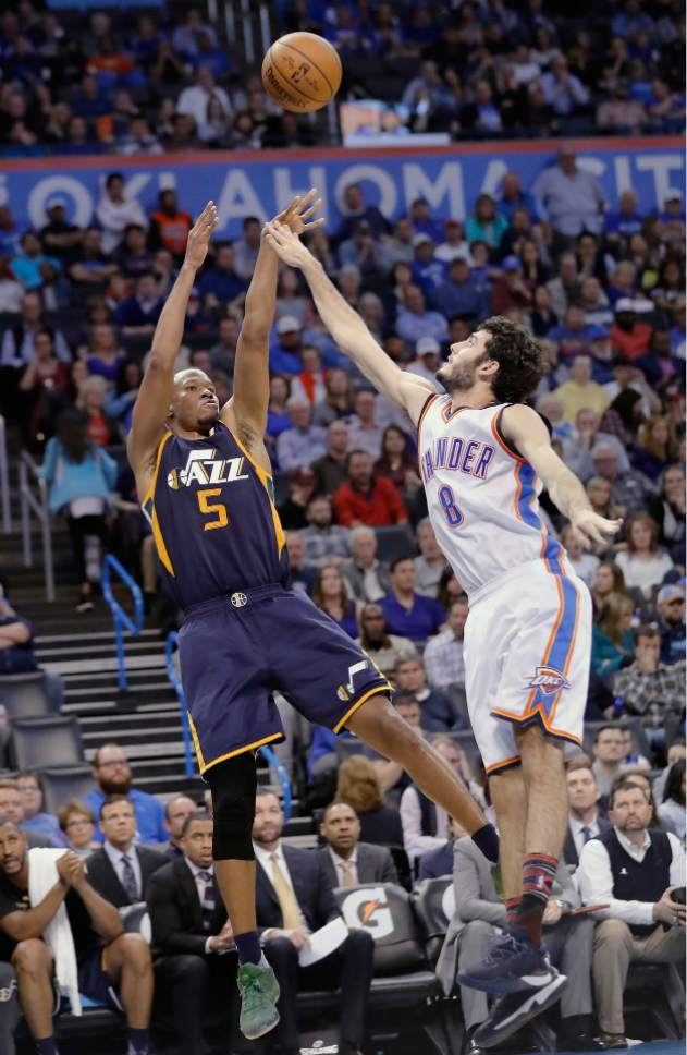 Utah Jazz guard Rodney Hood (5) shoots as Oklahoma City Thunder guard Alex Abrines (8) defends during the second half of an NBA basketball game in Oklahoma City, Tuesday, Feb. 28, 2017. Oklahoma City won 109-106. (AP Photo/Alonzo Adams)