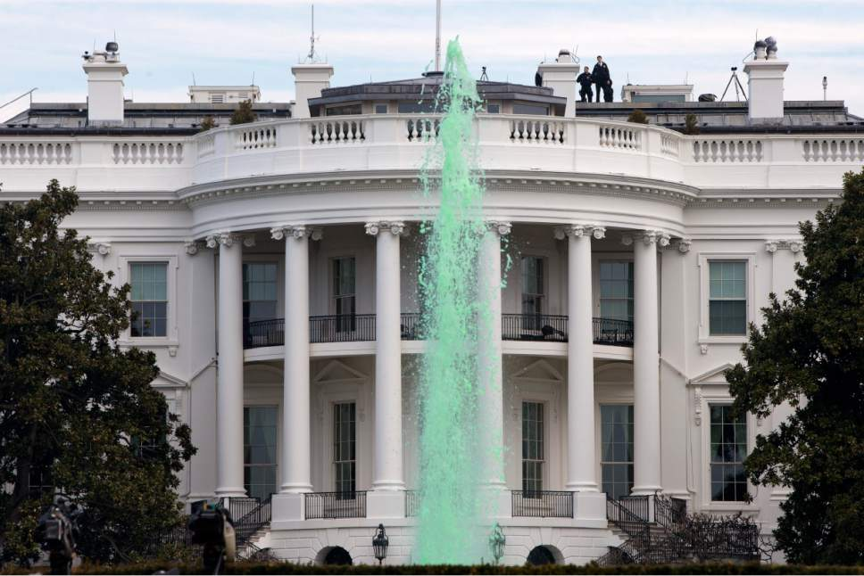 Members of the Secret Service patrol the top of the White House in Washington, Tuesday, March 17, 2015, as while a fountain has been dyed green for St. Patrick's Day. (AP Photo/Jacquelyn Martin)