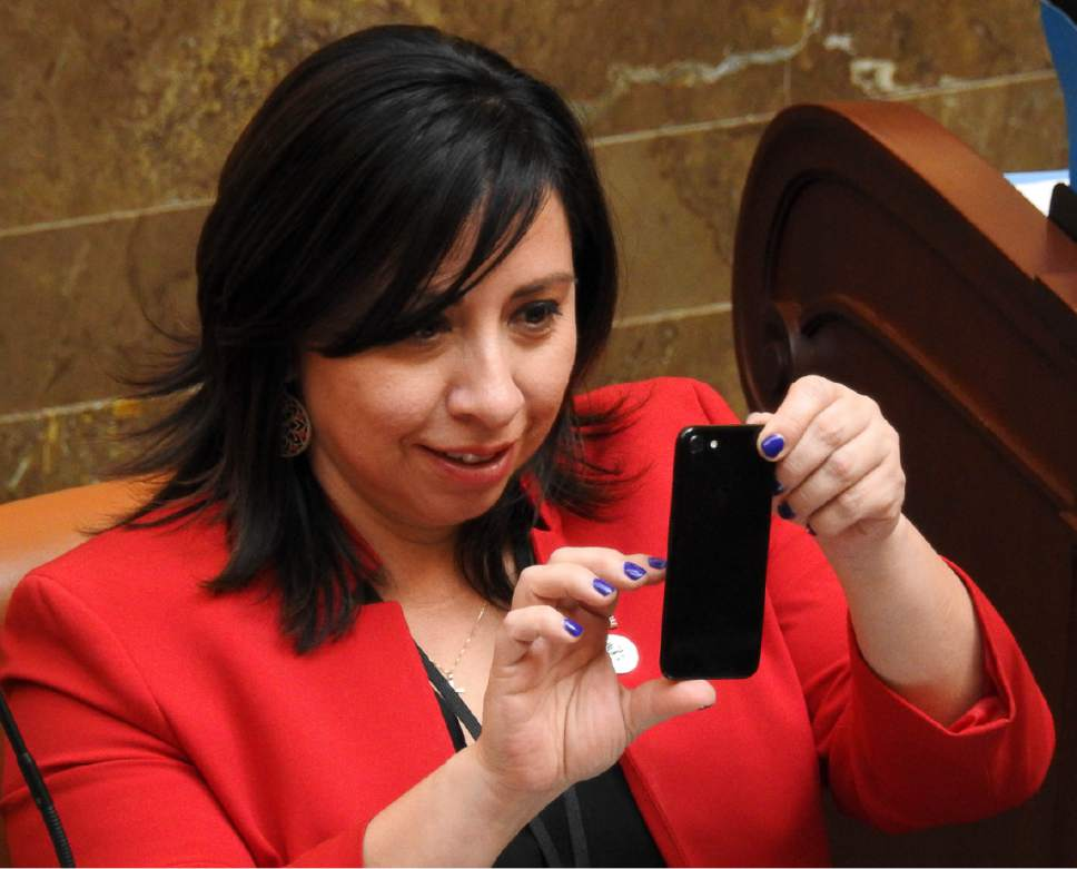 Trent Nelson  |  The Salt Lake Tribune Rep. Angela Romero, D-Salt Lake, takes a photo as the Utah House debates and passes SB159, which requires motorcyclists under 21 to wear a helmet, Wednesday March 8, 2017 in Salt Lake City.