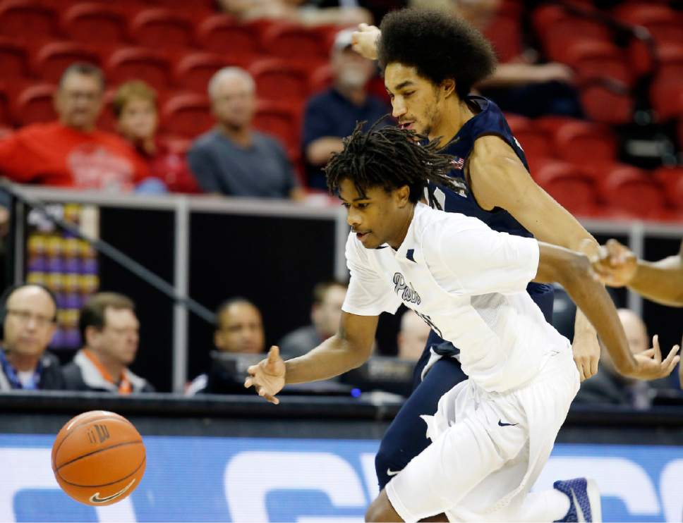 Utah State's Jalen Moore, right, and Nevada's Lindsey Drew go after a loose ball during the first half of an NCAA college basketball game in the Mountain West Conference tournament Thursday, March 9, 2017, in Las Vegas. (AP Photo/Isaac Brekken)