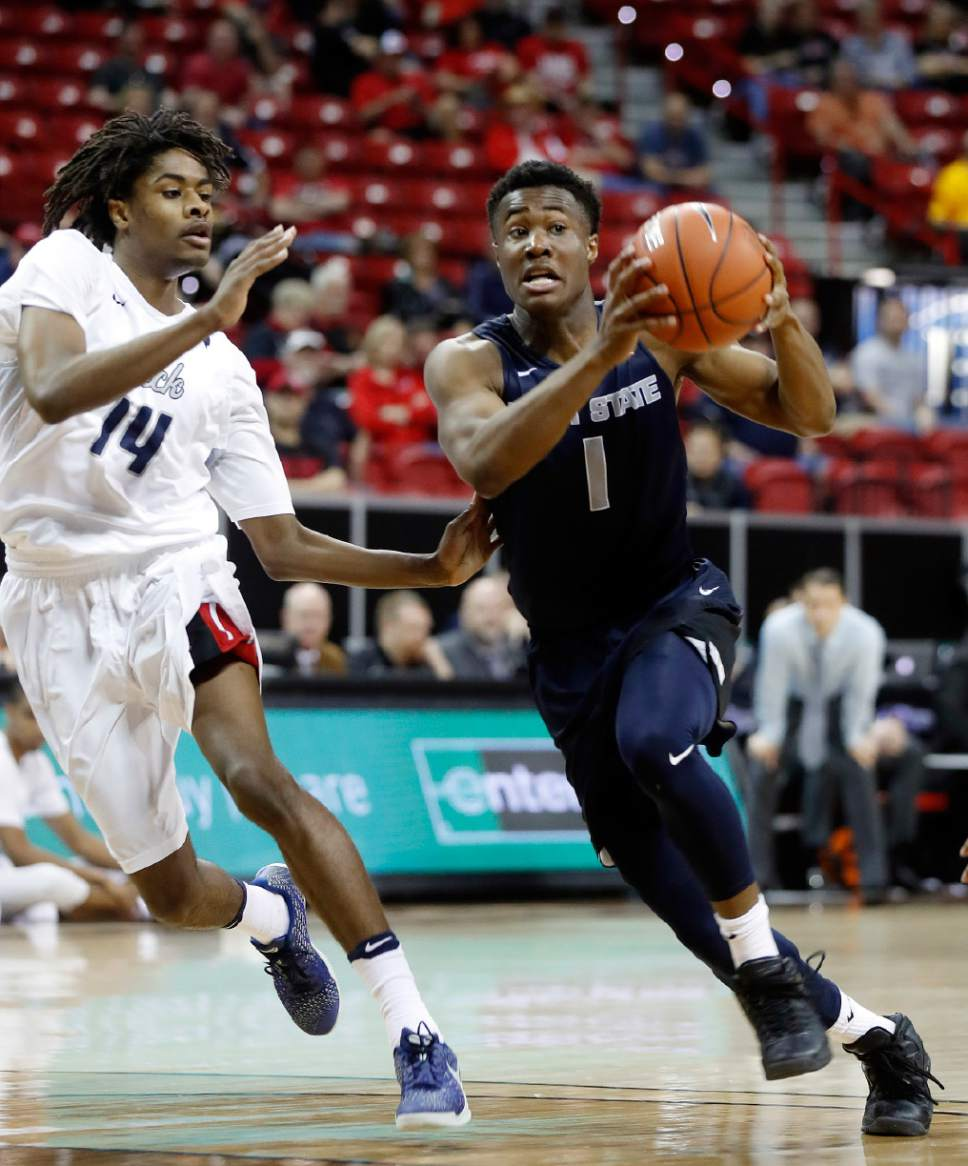 Utah State's Koby McEwen, of Canada, right drives to the hoop as Nevada's Lindsey Drew defends during the second half of an NCAA college basketball game in the Mountain West Conference tournament Thursday, March 9, 2017, in Las Vegas. (AP Photo/Isaac Brekken)