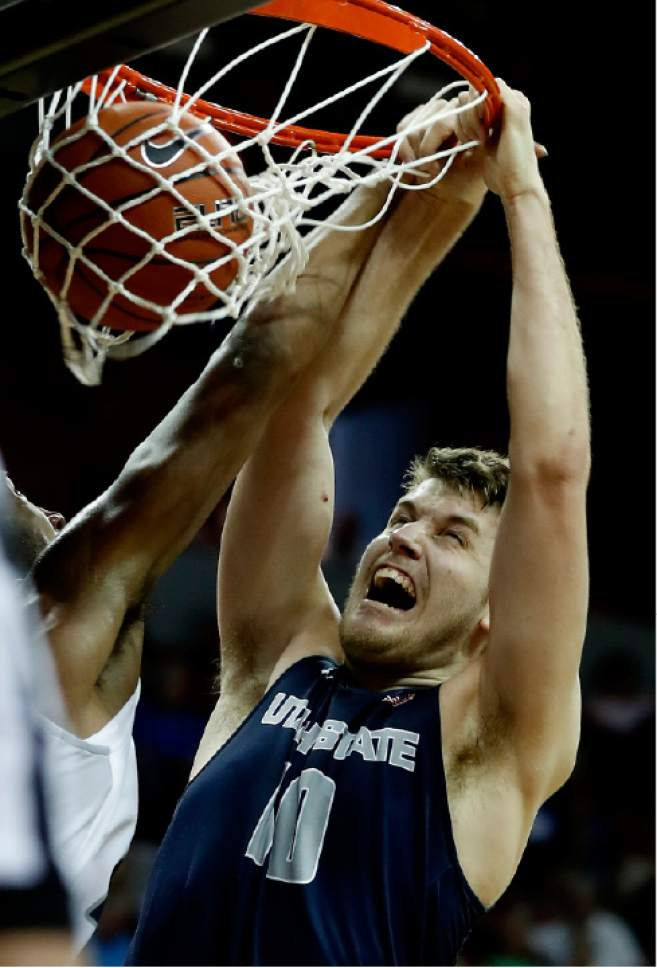 Utah State's Quinn Taylor dunks during the second half of an NCAA college basketball game against Nevada in the Mountain West Conference tournament Thursday, March 9, 2017, in Las Vegas. Nevada defeated Utah State 83-69. (AP Photo/Isaac Brekken)