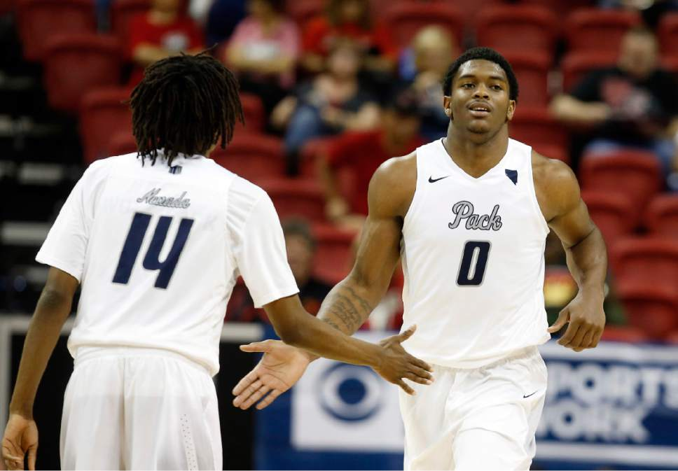 Nevada's Lindsey Drew, left, congratulates teammate Cameron Oliver after a play during the second half of an NCAA college basketball game against Utah State in the Mountain West Conference tournament Thursday, March 9, 2017, in Las Vegas. Nevada defeated Utah State 83-69. (AP Photo/Isaac Brekken)