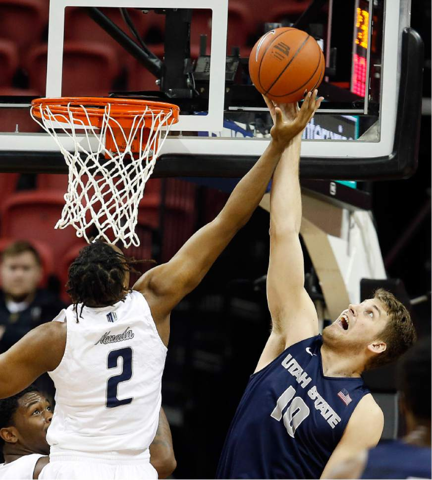 Utah State's Quinn Taylor, right, and Nevada's Leland King reach for a rebound during the first half of an NCAA college basketball game in the Mountain West Conference tournament Thursday, March 9, 2017, in Las Vegas. (AP Photo/Isaac Brekken)