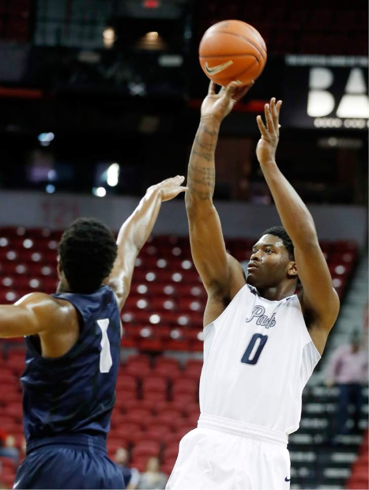 Nevada's Cameron Oliver shoots as Utah State's Koby McEwen, of Canada, defends during the first half of an NCAA college basketball game in the Mountain West Conference tournament Thursday, March 9, 2017, in Las Vegas. (AP Photo/Isaac Brekken)
