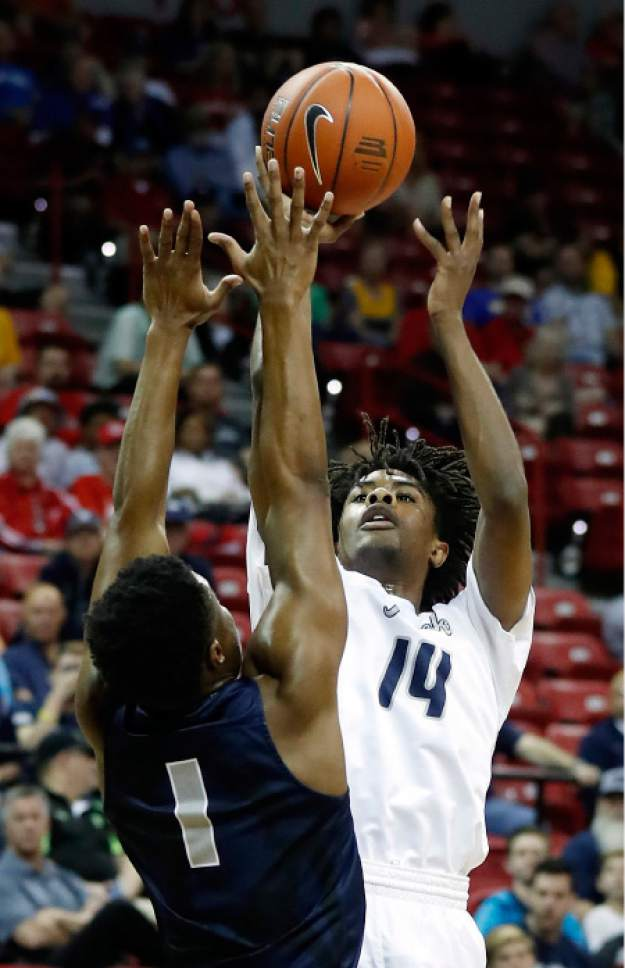 Nevada's Lindsey Drew shoots as Utah State's Koby McEwen, of Canada, defends during the first half of an NCAA college basketball game in the Mountain West Conference tournament Thursday, March 9, 2017, in Las Vegas. (AP Photo/Isaac Brekken)