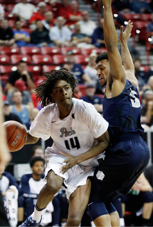 Nevada's Lindsey Drew drives under the hoop as Utah State's Julion Pearre defends during the first half of an NCAA college basketball game in the Mountain West Conference tournament Thursday, March 9, 2017, in Las Vegas. (AP Photo/Isaac Brekken)