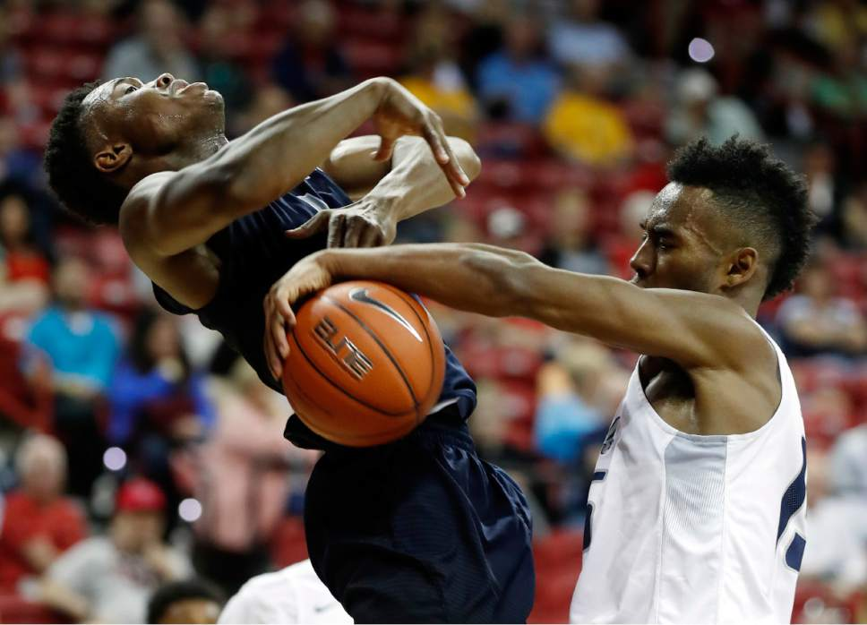 Utah State's Koby McEwen, left, of Canada, shoots as Nevada's D.J. Fenner defends during the second half of an NCAA college basketball game in the Mountain West Conference tournament Thursday, March 9, 2017, in Las Vegas. Nevada defeated Utah State 83-69. (AP Photo/Isaac Brekken)