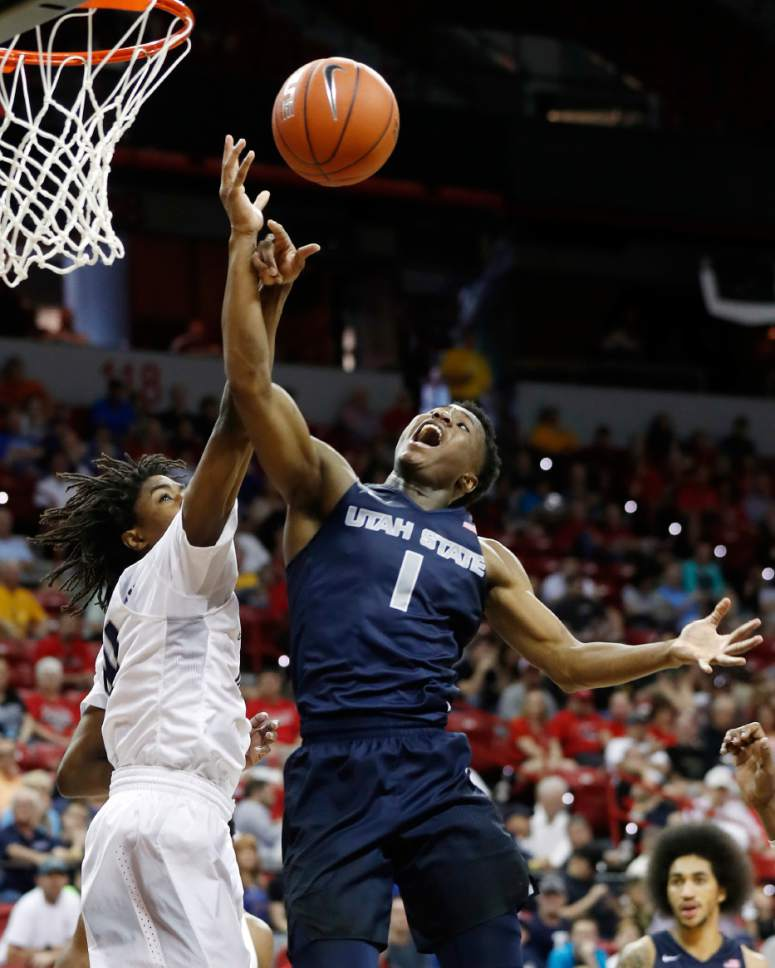 Utah State's Koby McEwen, of Canada, right, shoots as Nevada's Lindsey Drew defends during the second half of an NCAA college basketball game in the Mountain West Conference tournament Thursday, March 9, 2017, in Las Vegas. Nevada defeated Utah State 83-69. (AP Photo/Isaac Brekken)
