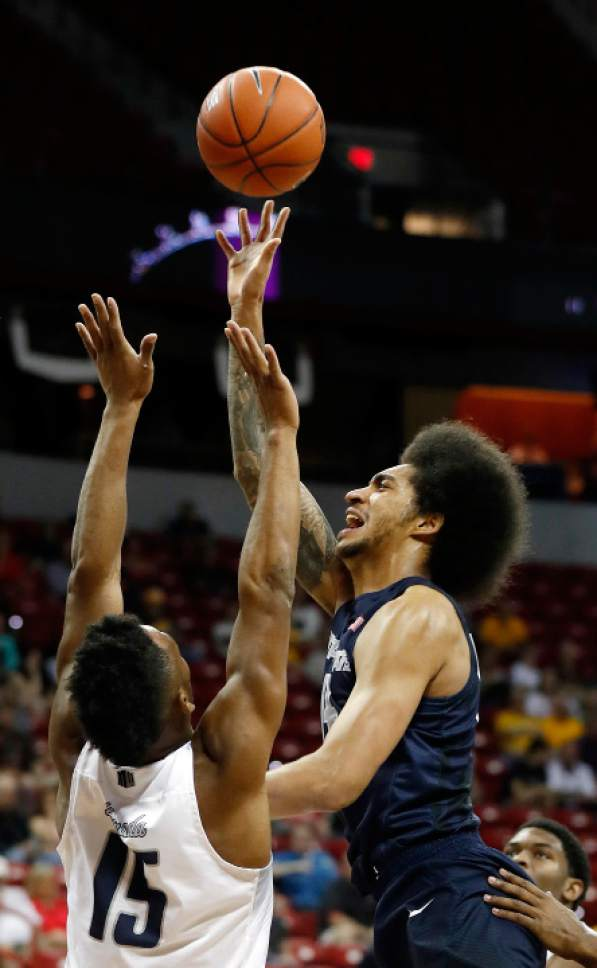 Utah State's Jalen Moore, right, shoots as Nevada's D.J. Fenner defends during the second half of an NCAA college basketball game in the Mountain West Conference tournament Thursday, March 9, 2017, in Las Vegas.  (AP Photo/Isaac Brekken)