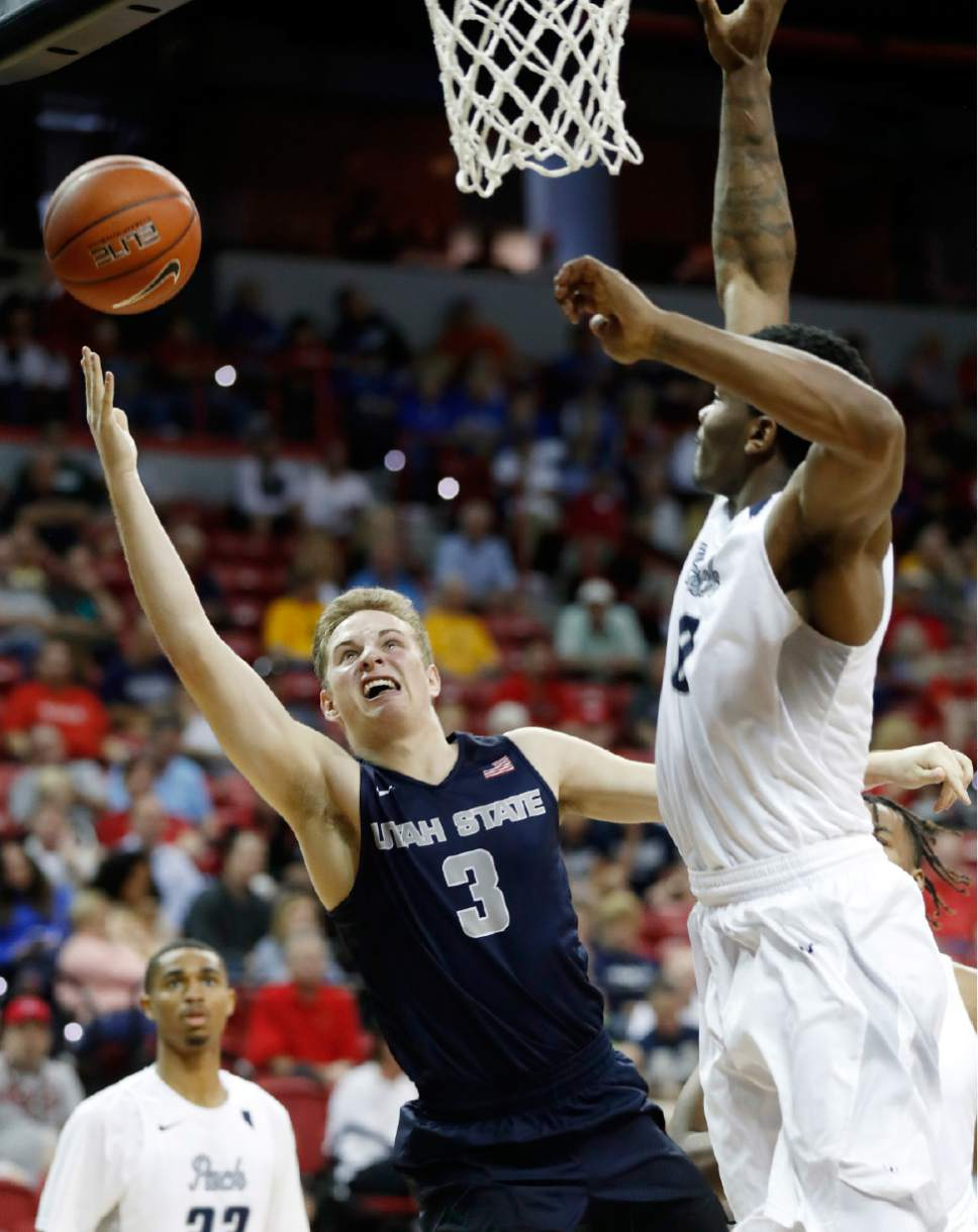 Utah State's Sam Merrill shoots as Nevada's Leland King Jr. defends during the second half of an NCAA college basketball game in the Mountain West Conference tournament Thursday, March 9, 2017, in Las Vegas. Nevada defeated Utah State 83-69. (AP Photo/Isaac Brekken)