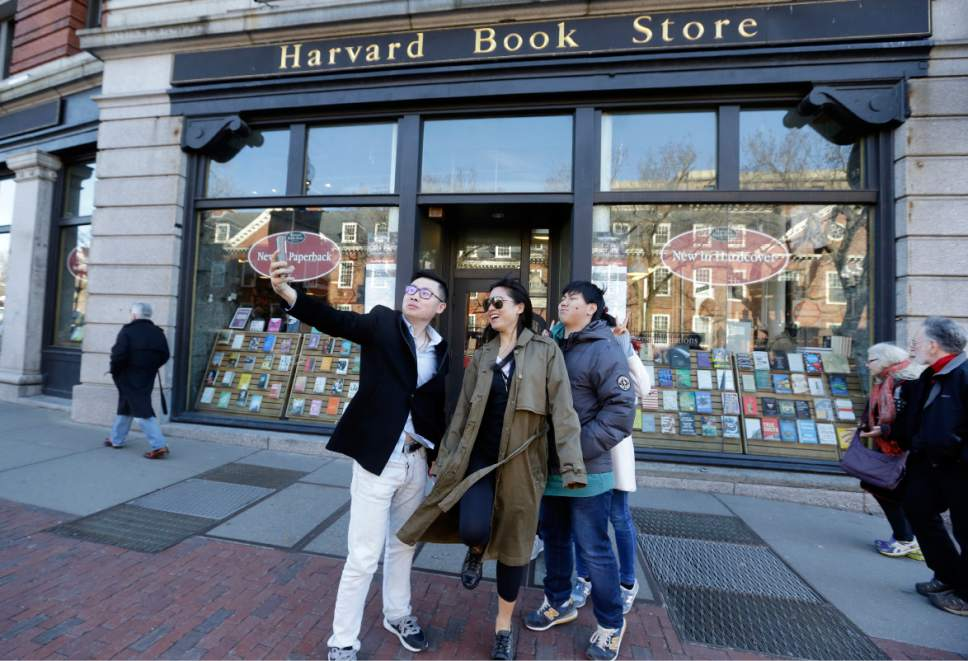 "Students pose for a selfie outside the Harvard Book Store, Thursday, March 9, 2017, in Cambridge, Mass. Readers have been flocking to classic works of dystopian fiction in the first months of Donald Trump's presidency. Novels depicting dysfunctional societies have shot to the top of best-seller lists in recent months, including George Orwell's ""1984"" and Margaret Atwood's ""The Handmaid's Tale."" Publishers credit Trump's election for sparking demand. (AP Photo/Elise Amendola)"