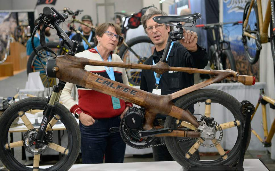 "Al Hartmann  |  The Salt Lake Tribune Debra Banks, a hand crafted saddle manufacturer for Rivet Cycle Works, left, checks out a one of a kind ""Big Bamboo Bike"" made by Craig Calfee of Calfee Designs out of Santa Cruz, CA. at the 2017 North American Handmade Bicycle Show at the Salt Palace Convention Center Friday March 10.  This model is an electric bike made of a bamboo including the wheel spokes.  The battery is inside the large tube. He makes several more coventional design custom bicycles using bamboo frames.   It's the largest and oldest handbuilt bicycle show in the world where ideas and innovation come together to promote custom bicycles and the companies that support the market.  It's the show's first time in Utah. The event runs Friday, March 10, to Sunday, March 12.at the 2017 North American Handmade Bicycle Show at the Salt Palace Convention Center Friday March 10."