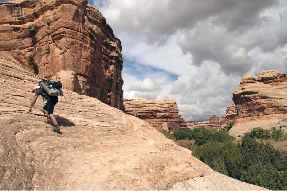 Al Hartmann  |  The Salt Lake Tribune  Backpacker climbs a sandstone ramp in a canyon on Cedar Mesa in a part of San Juan County that is now Bears Ears National Monument.