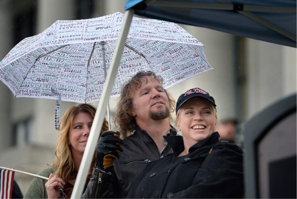 Scott Sommerdorf      The Salt Lake Tribune   Polygamist Kody Brown listens to his wife Christine speak to polygamists and their supporters at a rally on the south steps of the Capitol, Friday, Feb. 10, 2017.