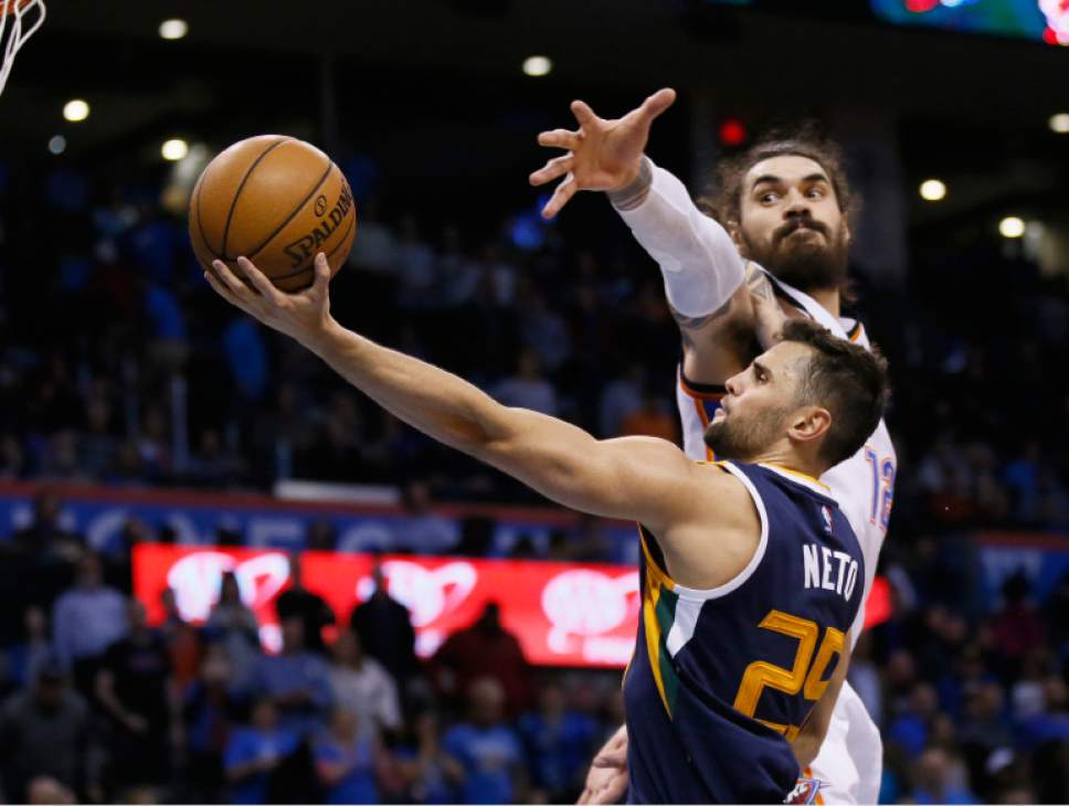 Utah Jazz guard Raul Neto, front, shoots in front of Oklahoma City Thunder center Steven Adams, rear, in the fourth quarter of an NBA basketball game in Oklahoma City, Saturday, March 11, 2017. Oklahoma City won 112-104. (AP Photo/Sue Ogrocki)