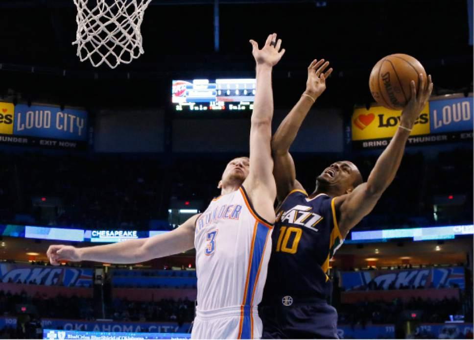 Utah Jazz guard Alec Burks shoots as Oklahoma City Thunder forward Domantas Sabonis (3) defends in the second quarter of an NBA basketball game in Oklahoma City, Saturday, March 11, 2017. Oklahoma City won 112-104. (AP Photo/Sue Ogrocki)