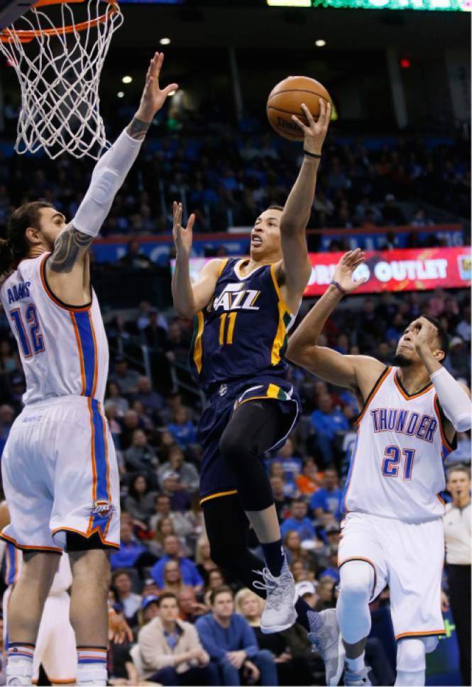 Utah Jazz guard Dante Exum (11) shoots between Oklahoma City Thunder center Steven Adams (12) and forward Andre Roberson (21) in the fourth quarter of an NBA basketball game in Oklahoma City, Saturday, March 11, 2017. Oklahoma City won 112-104. (AP Photo/Sue Ogrocki)