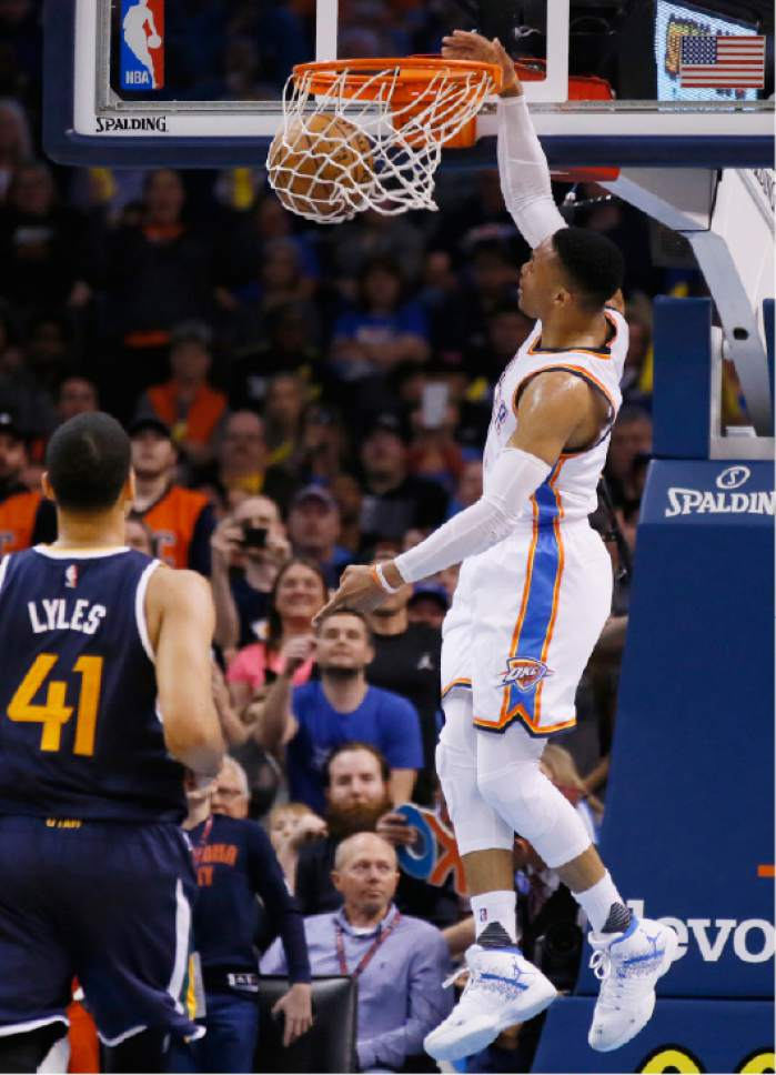 Oklahoma City Thunder guard Russell Westbrook, right, dunks in front of Utah Jazz forward Trey Lyles (41) in the third quarter of an NBA basketball game in Oklahoma City, Saturday, March 11, 2017. Oklahoma City won 112-104. (AP Photo/Sue Ogrocki)