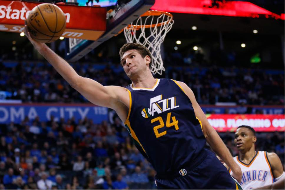 Utah Jazz center Jeff Withey (24) reaches to keep the ball from going out of bounds in front of Oklahoma City Thunder guard Russell Westbrook, right, in the third quarter of an NBA basketball game in Oklahoma City, Saturday, March 11, 2017. Oklahoma City won 112-104. (AP Photo/Sue Ogrocki)