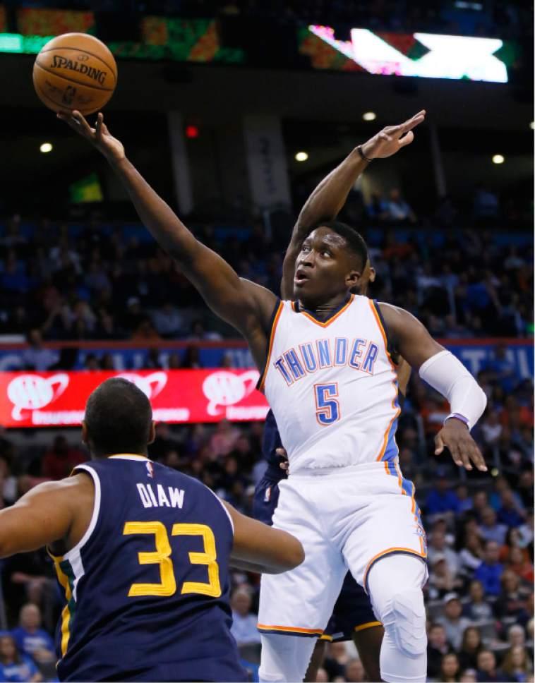 Oklahoma City Thunder guard Victor Oladipo (5) shoots between Utah Jazz center Boris Diaw (33) and forward Joe Johnson, rear, in the second quarter of an NBA basketball game in Oklahoma City, Saturday, March 11, 2017. (AP Photo/Sue Ogrocki)