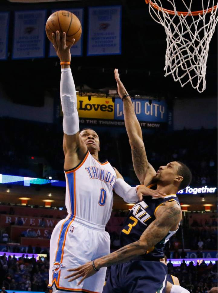 Oklahoma City Thunder guard Russell Westbrook (0) shoots as Utah Jazz guard George Hill (3) defends in the first quarter of an NBA basketball game in Oklahoma City, Saturday, March 11, 2017. (AP Photo/Sue Ogrocki)