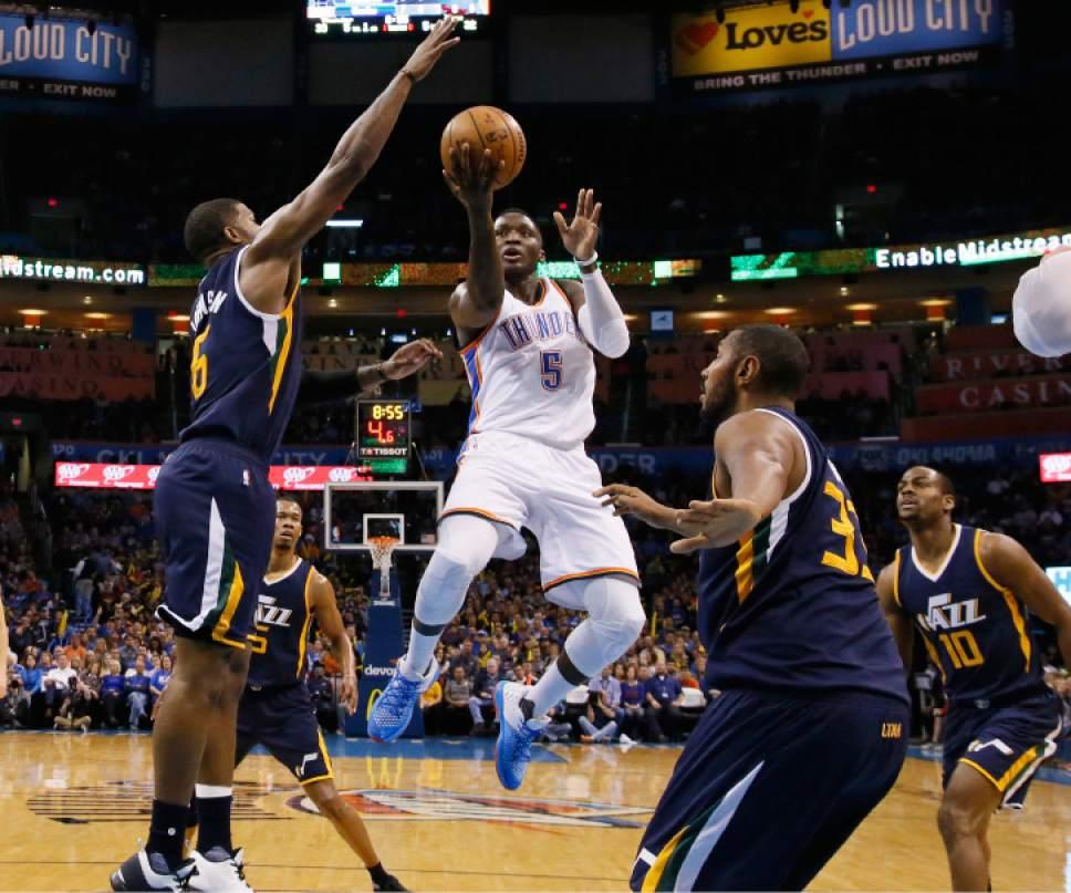 Oklahoma City Thunder guard Victor Oladipo (5) shoots between Utah Jazz forward Joe Johnson (6), guard Rodney Hood (5), center Boris Diaw (33) and guard Alec Burks (10) in the second quarter of an NBA basketball game in Oklahoma City, Saturday, March 11, 2017. (AP Photo/Sue Ogrocki)