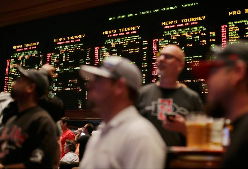 FILE - In this March 22, 2013, file photo, odds for second-round NCAA basketball tournament games are displayed on a board at the Mirage hotel-casino Race & Sports Book in Las Vegas. With 70 million-plus office pool brackets, Americans will put in the neighborhood of $2 billion at stake on the NCAA Tournament this week.  (AP Photo/Julie Jacobson, File)