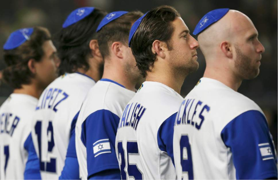 Israel's catcher Nick Rickles, right, pitcher Jake Kalish, second from right, and other players listen to their national anthem during the opening ceremony of their second round game against the Netherlands at the World Baseball Classic at Tokyo Dome in Tokyo, Monday, March 13, 2017. (AP Photo/Koji Sasahara)