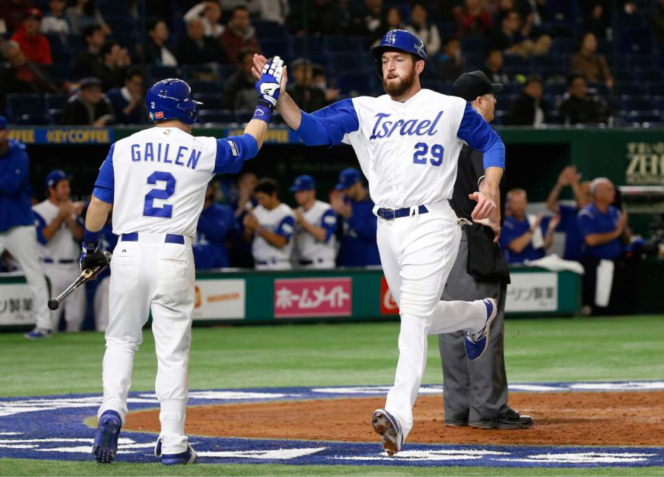 Israel's Ike Davis, right, celebrates with teammate Tyler Krieger at home after scoring on Ryan Lavarnway's double against Cuba during the fourth inning of their second round game of the World Baseball Classic at Tokyo Dome in Tokyo, Sunday, March 12, 2017. (AP Photo/Shizuo Kambayashi)