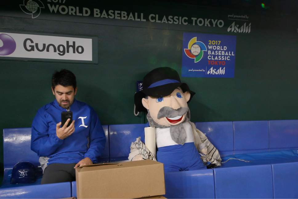 "Israel's baseball team member uses a smart phone next to the teams mascot ""The Mensch on the Bench"" prior to the second round game between Israel and Cuba at the World Baseball Classic at Tokyo Dome in Tokyo, Sunday, March 12, 2017. (AP Photo/Shizuo Kambayashi)"