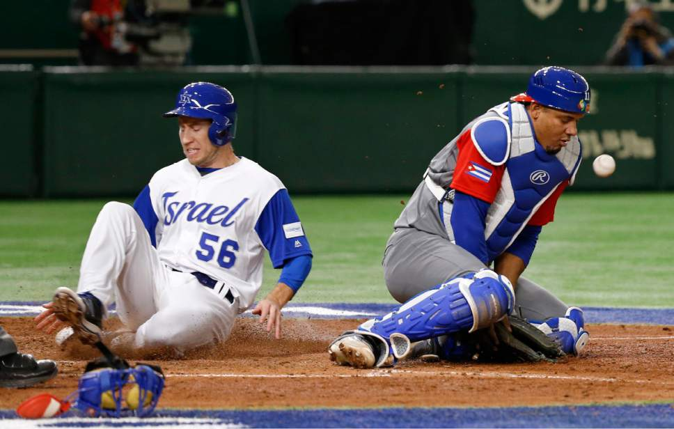 Israel's Ty Kelly scores past Cuba's catcher Yosvani Alarcon in the sixth inning of their second round game of the World Baseball Classic at Tokyo Dome in Tokyo, Sunday, March 12, 2017. (AP Photo/Shizuo Kambayashi)