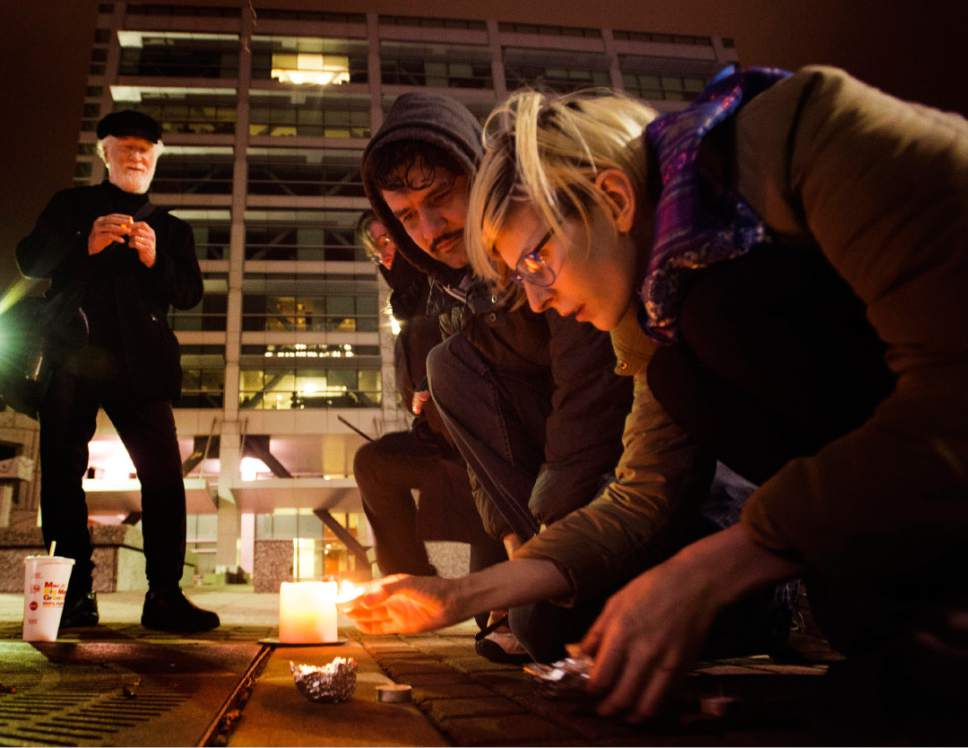 Rick Egan  |  The Salt Lake Tribune  Mark Koopman, Michelle Butler, Hann Mathews and Juniper Monypenny light candles at the Federal Building, Monday, February 20, 2017.