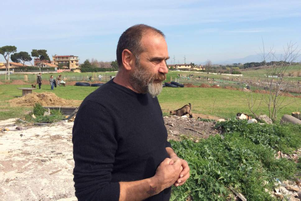 Squatter activist Omero Lauri observes farmers working their plots of land in Tor Tre Teste neighborhood, in Rome, Sunday, March 12, 2017. Dozens of families have started farming plots of land, tilling the soil and planting their first crops as a squatters' gardening initiative has taken root on Catholic Church-owned land with the nominal blessing of Pope Francis. (AP Photo/Nicole Winfield)