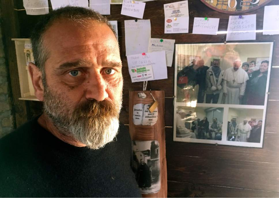 Squatter activist Omero Lauri poses next to Dec. 1, 2013 photographs of him and other squatters with Pope Francis hanging inside a makeshift farmhouse in Tor Tre Teste neighborhood, Rome, Sunday, March 12, 2017. Dozens of families have started farming plots of land, tilling the soil and planting their first crops as a squatters' gardening initiative has taken root on Catholic Church-owned land with the nominal blessing of Pope Francis. (AP Photo/Paolo Santalucia)