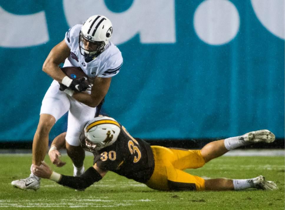 Rick Egan  |  The Salt Lake Tribune  Brigham Young Cougars wide receiver Moroni Laulu-Pututau (1) runs through the tackle of Wyoming linebacker Logan Wilson (30) during their game at Qualcomm Stadium in San Diego, Dec. 21, 2016.