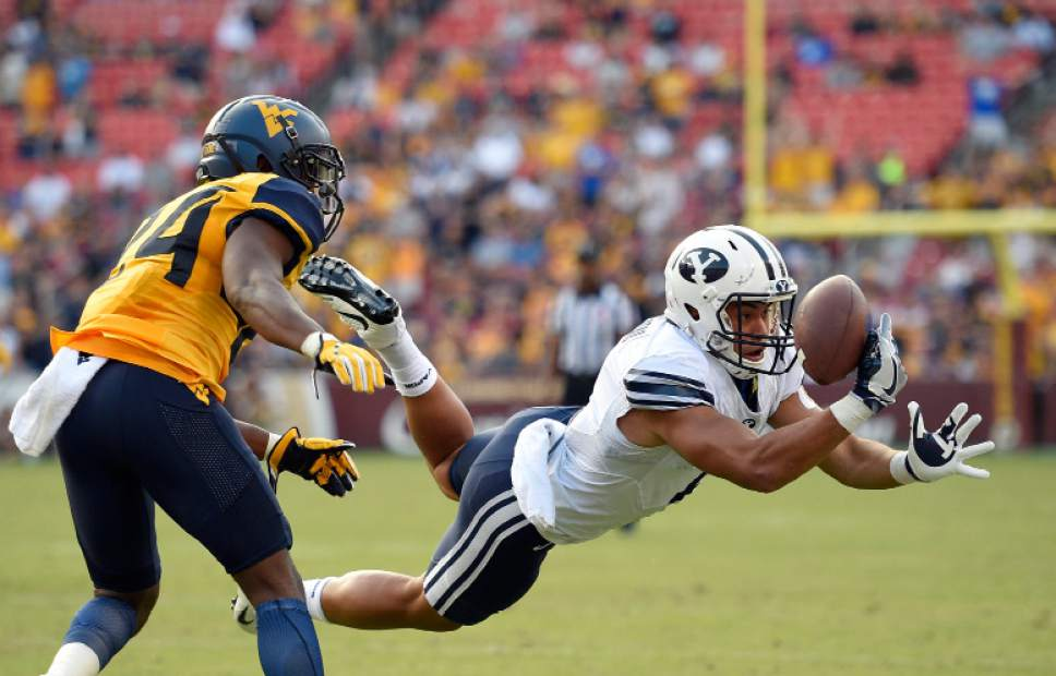 BYU wide receiver Moroni Laulu-Pututau, right, cannot hold onto the ball as a pass goes incomplete against West Virginia cornerback Maurice Fleming (24) during the second half of an NCAA college football game, Saturday, Sept. 24, 2016, in Landover, Md. (AP Photo/Nick Wass)