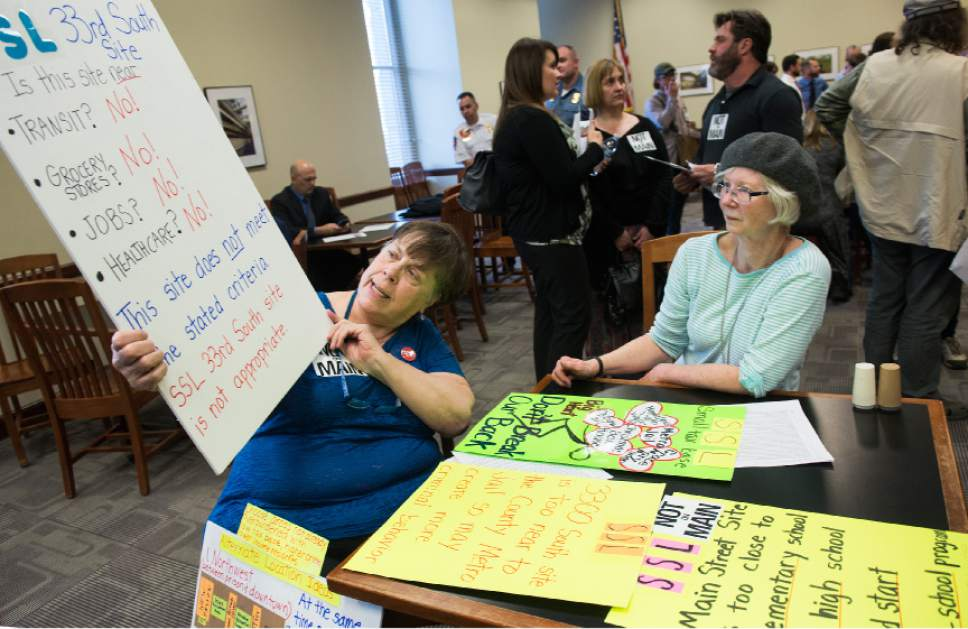Leah Hogsten  |  The Salt Lake Tribune l-r Neighbors Susan Bollden and Kim Deacon brought signs to illustrate why the site selections do not meet the county's criteria for a shelter. Hundreds of concerned citizens packed the state Capitol's Senate Building cafeteria Tuesday, March 14, 2017 during one of three  scheduled opportunities for the public to give feedback on possible shelter sites to Salt Lake County Mayor Ben McAdams and county staff.