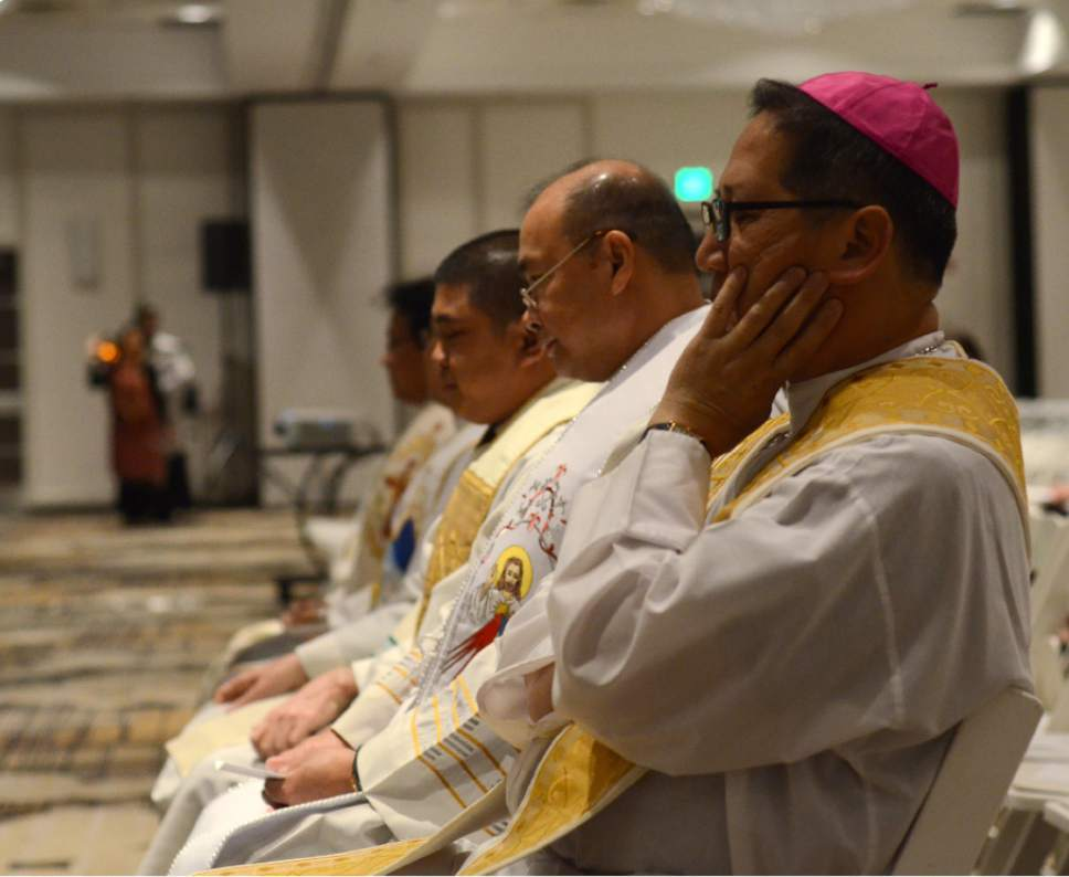 Mike Stack  |  for The Salt Lake Tribune  Bishop Oscar Solis in contemplation with other priests before Mass.