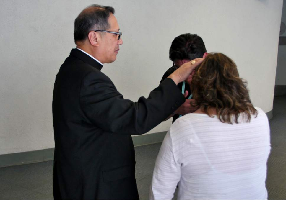 Mike Stack  |  for The Salt Lake Tribune  Bishop Oscar Solis blesses John Saavedra in hallway of the convention center.