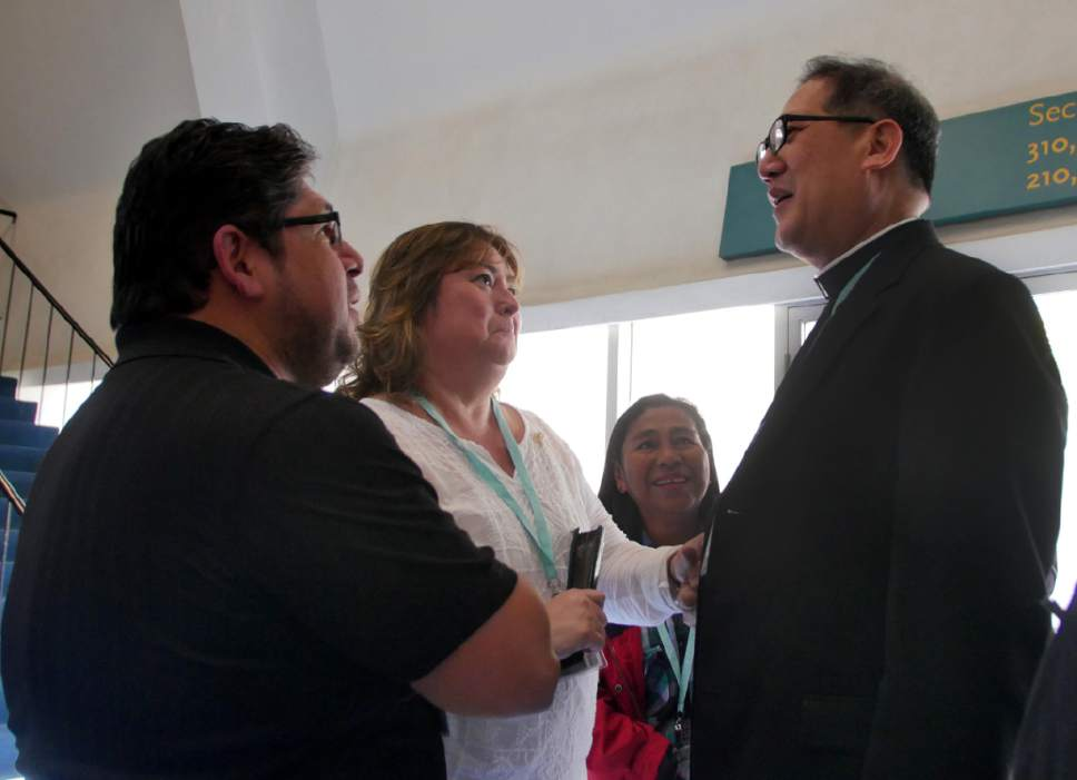 Mike Stack  |  for The Salt Lake Tribune  Bishop Solis speaks with Irma and John Saavedra.