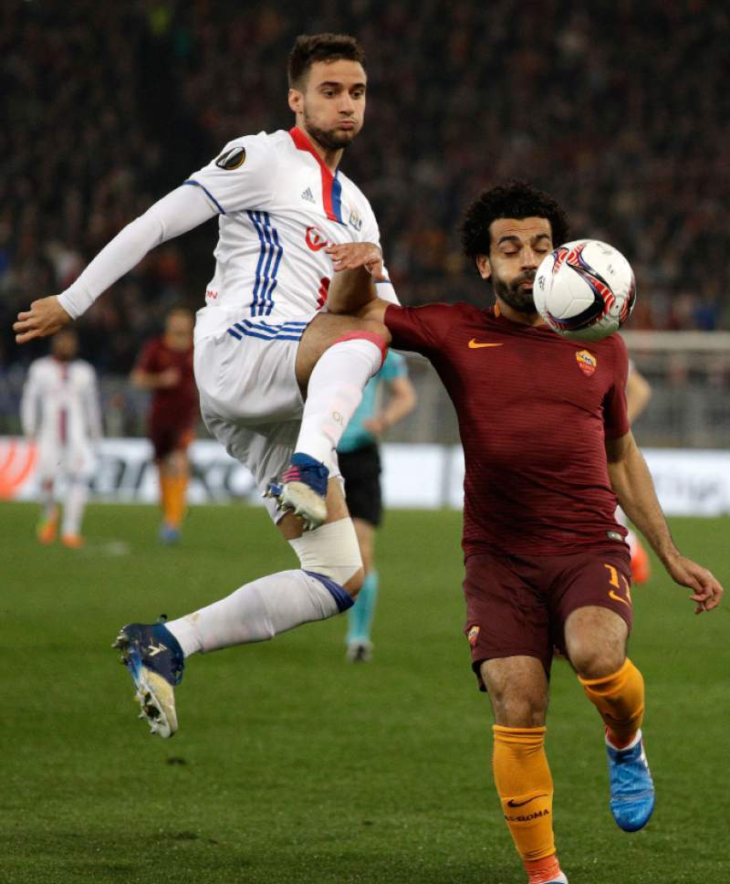 Lyon's Emanuel Mammana, left, challenges Roma's Mohamed Salah, right, during the Europa League round of 16 second leg soccer match between Roma and Lyon, in Rome's Olympic stadium, Thursday, March 16, 2017. (AP Photo/Andrew Medichini)